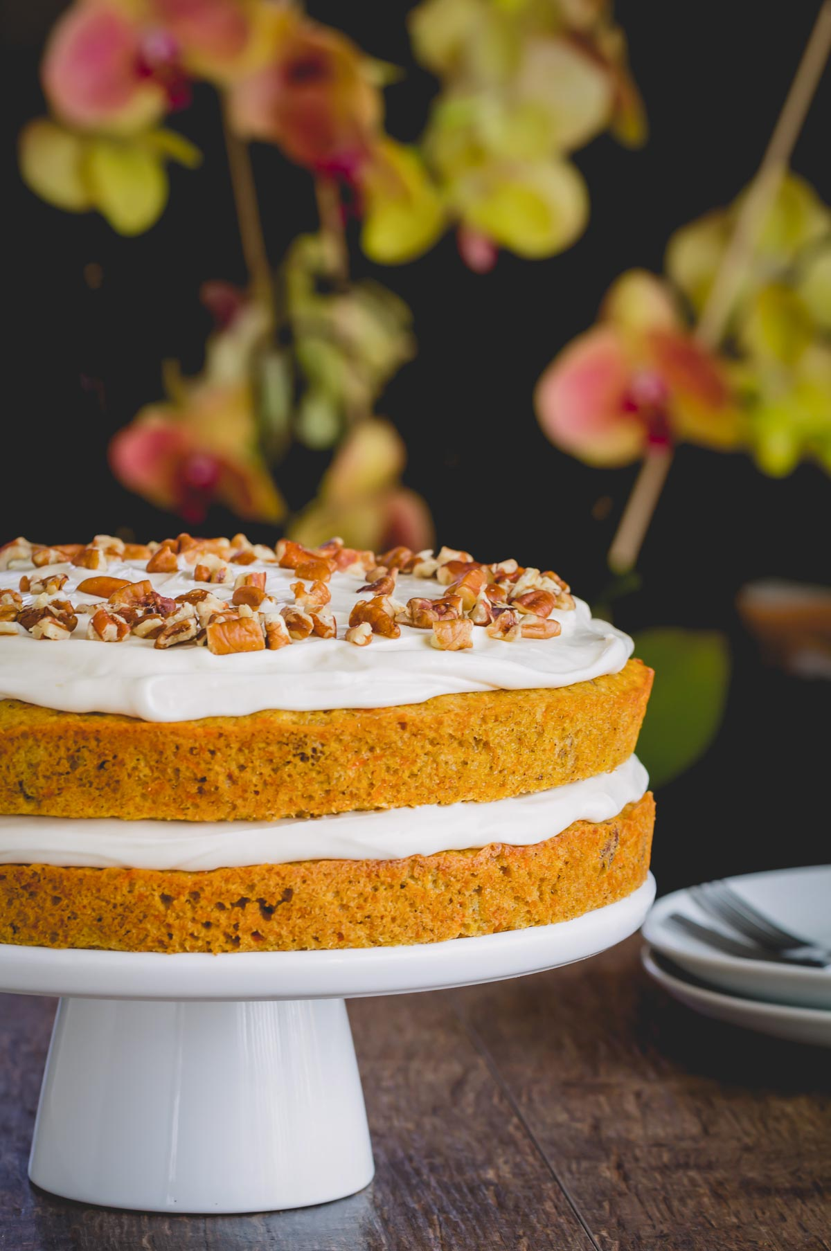 A whole carrot cake on a white cake platter.