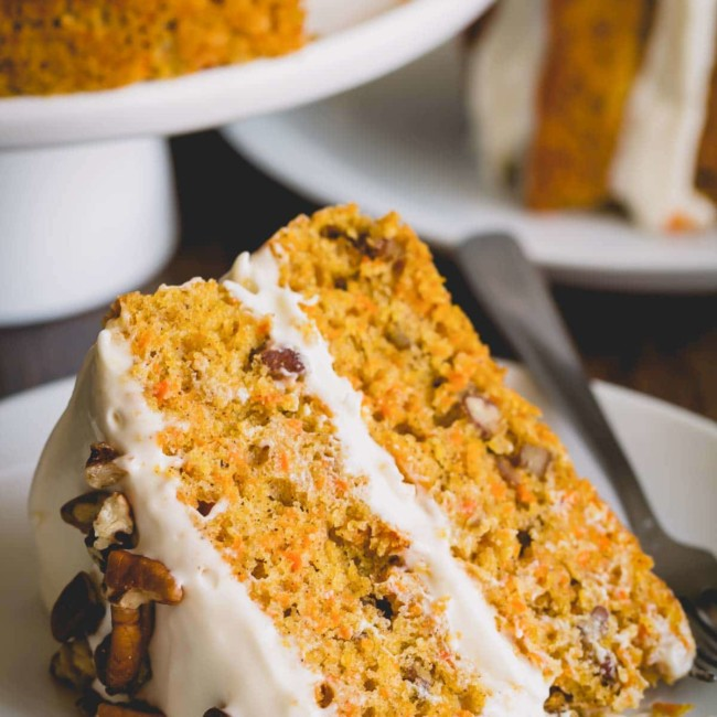Close-up shot of a slice of carrot cake on a white plate.