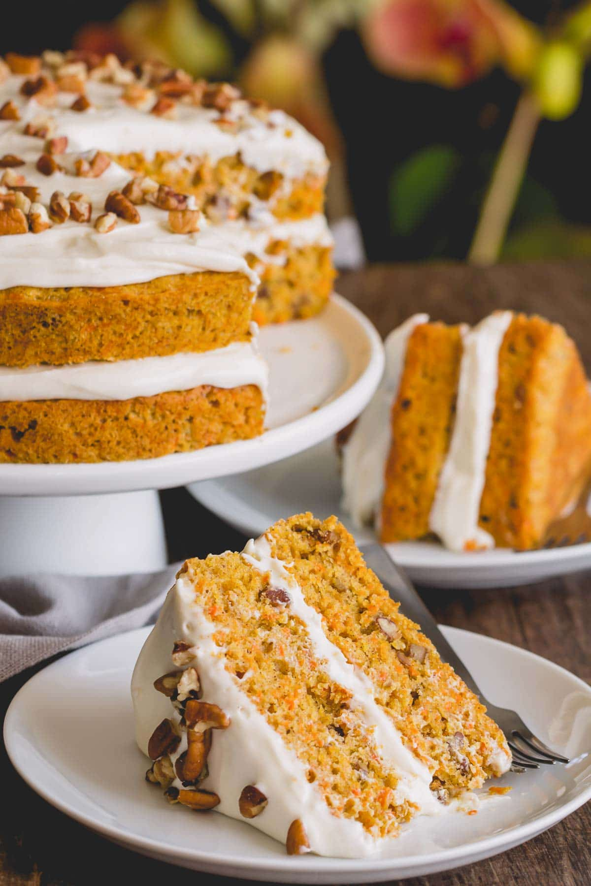 Slice of carrot cake on a white plate.
