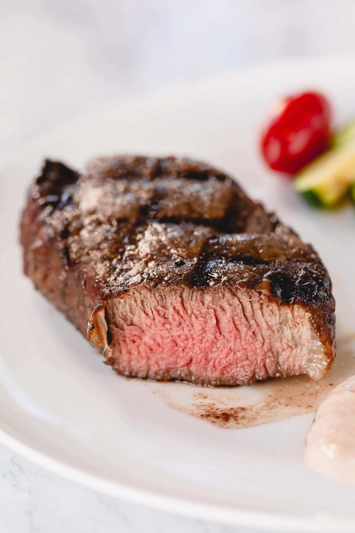 Grilled filet mignon on a white plate with a slice cut.