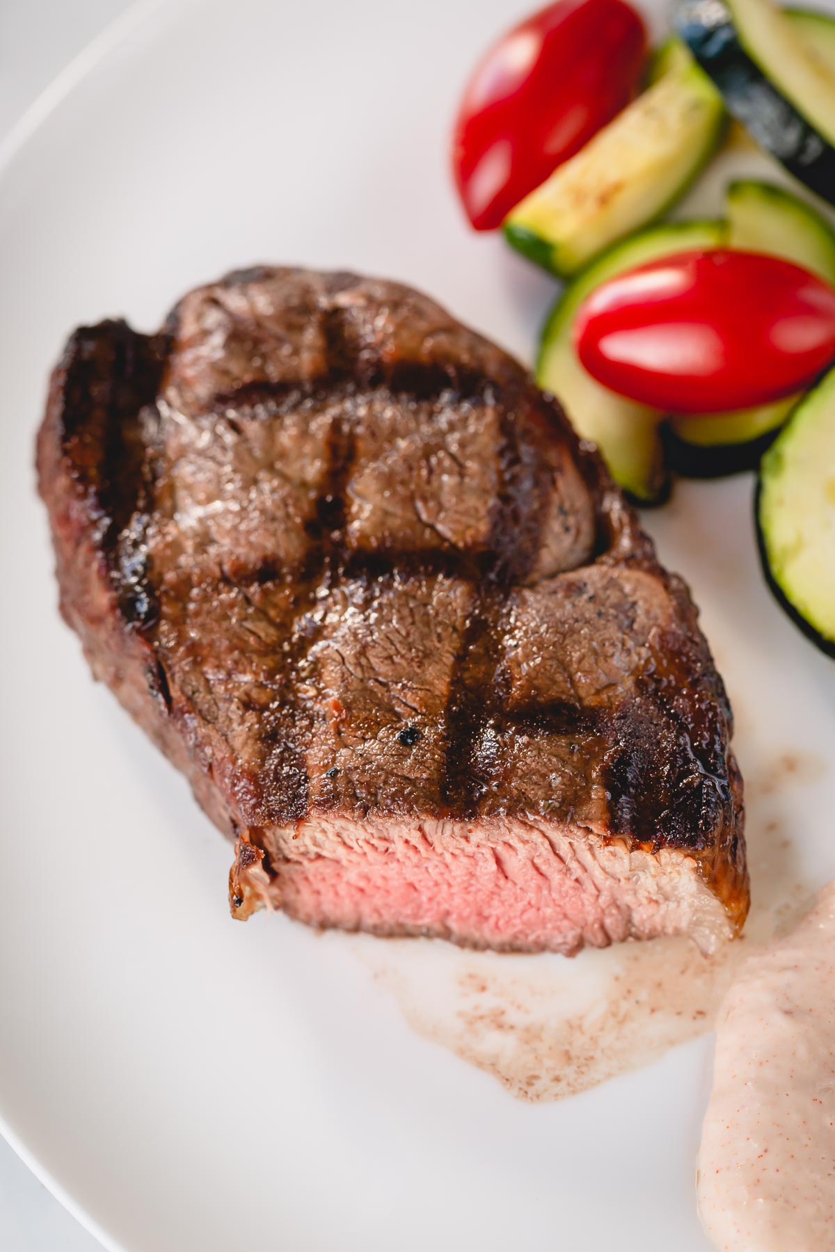 A whole grilled filet mignon on a white plate with zucchini and cherry tomatoes on the side.
