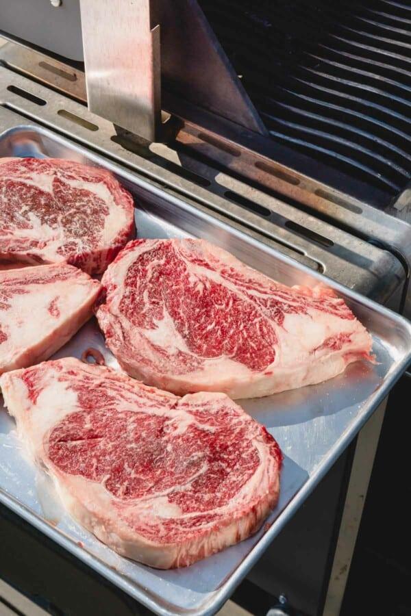 4 raw ribeye steaks on a baking sheet by a grill.