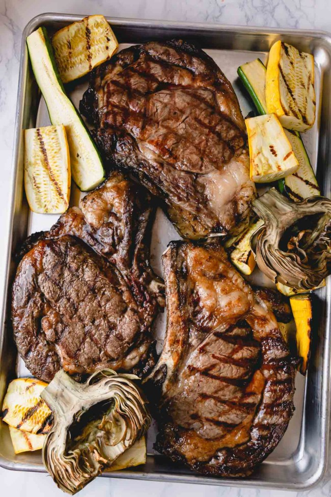 3 grilled ribeye steaks on a baking sheet with grilled zucchini and artichokes.