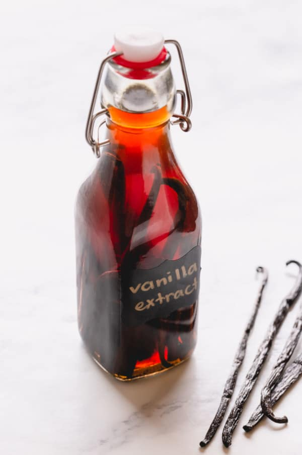 Homemade vanilla bean extract in a clear bottle.