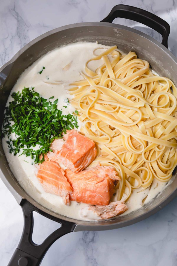 A skillet of cooked fettuccini, chunks of smoked salmon and chopped fresh parsley over a bed of alfredo sauce.