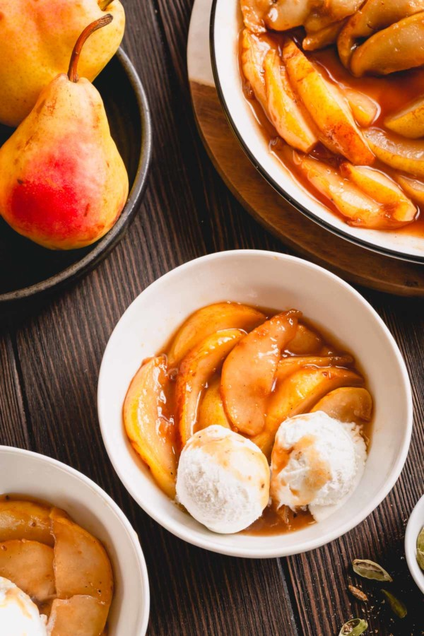 Caramelized pear slices with vanilla ice cream in a small bowl.