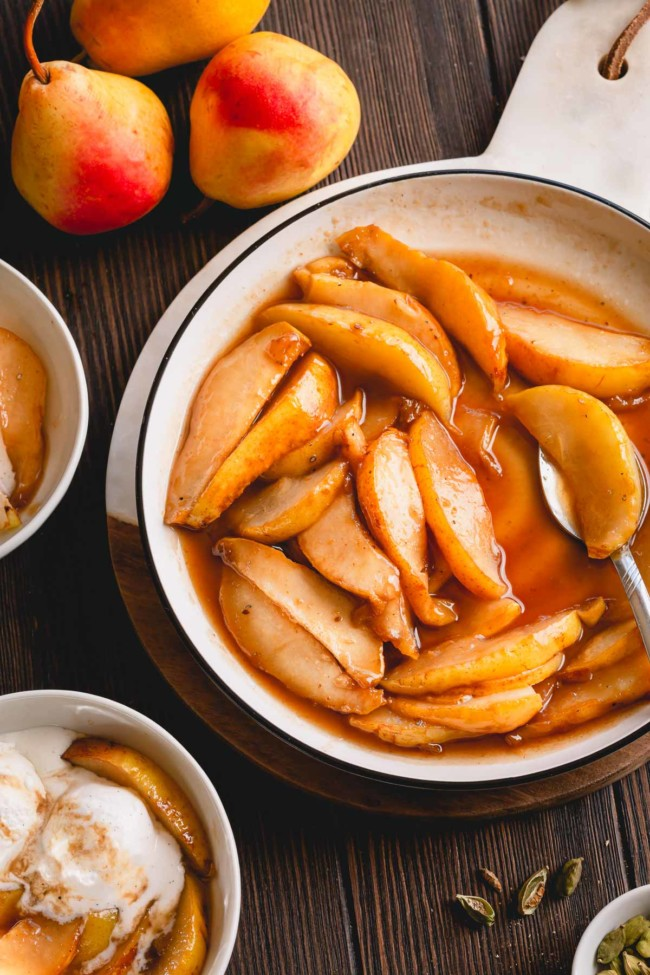Caramelized pear slices with sauce in a white plate.
