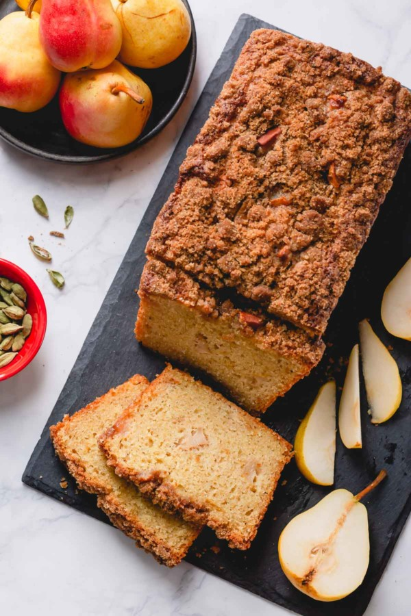 Overhead shot of pear bread on black cutting board with a few slices.