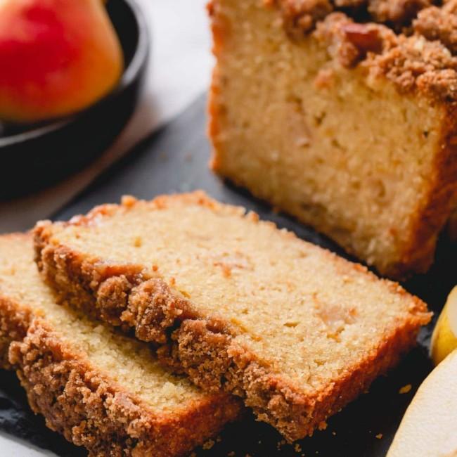 Closeup shot of pear bread slices on black cutting board.
