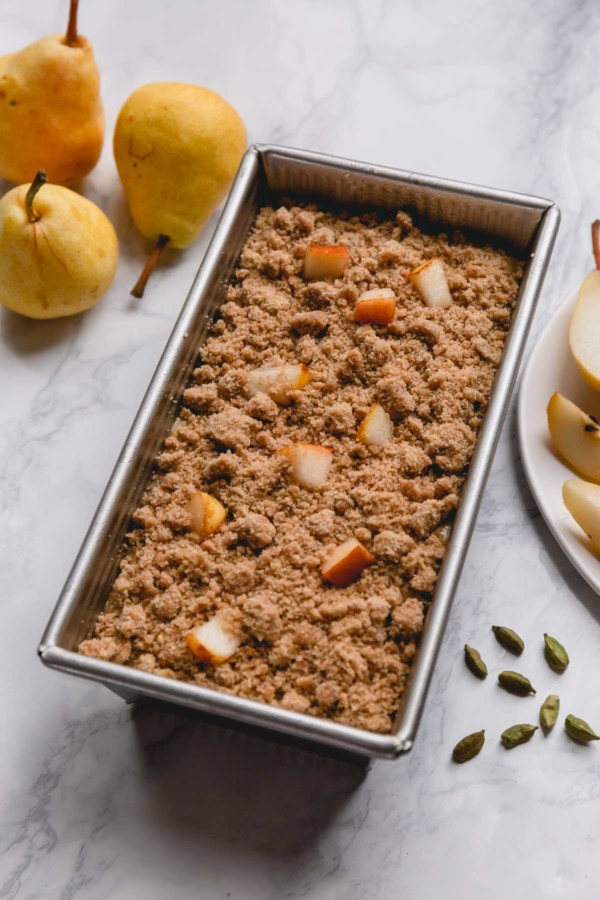 Uncooked pear bread in a loaf pan topped with streusel top and fresh pear chunks.