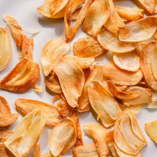Golden fried garlic slices on a white plate.