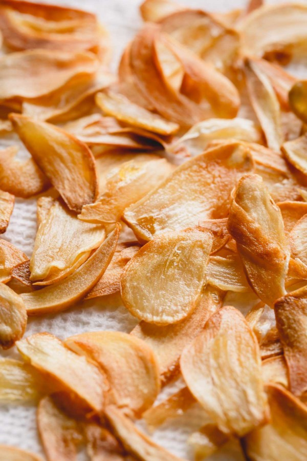 Upclose shot of fried garlic slices on a paper towel.