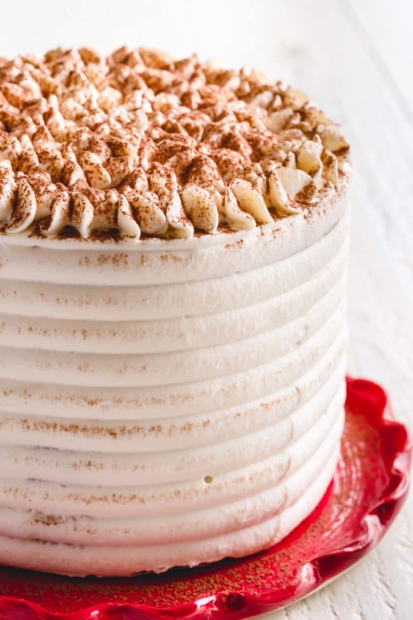 A whole tiramisu cake dusted with cocoa powder on a red plate.