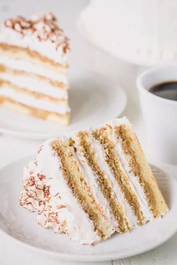 A slice of tiramisu layer cake on a white plate.