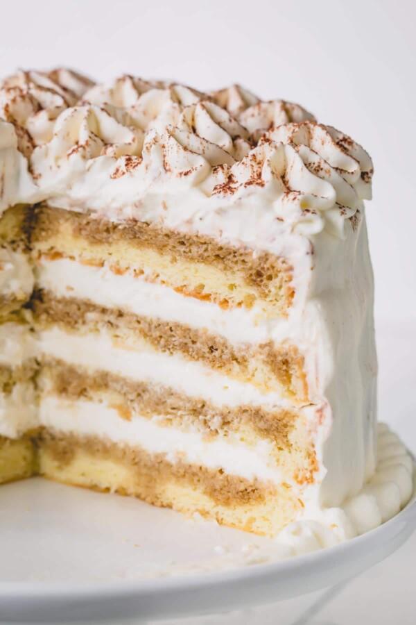 A cut version of a whole tiramisu layer cake on a white cake platter.