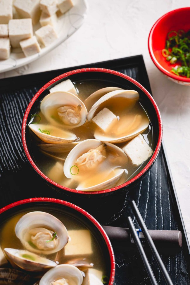 2 bowls of clam miso soup on a black tray.