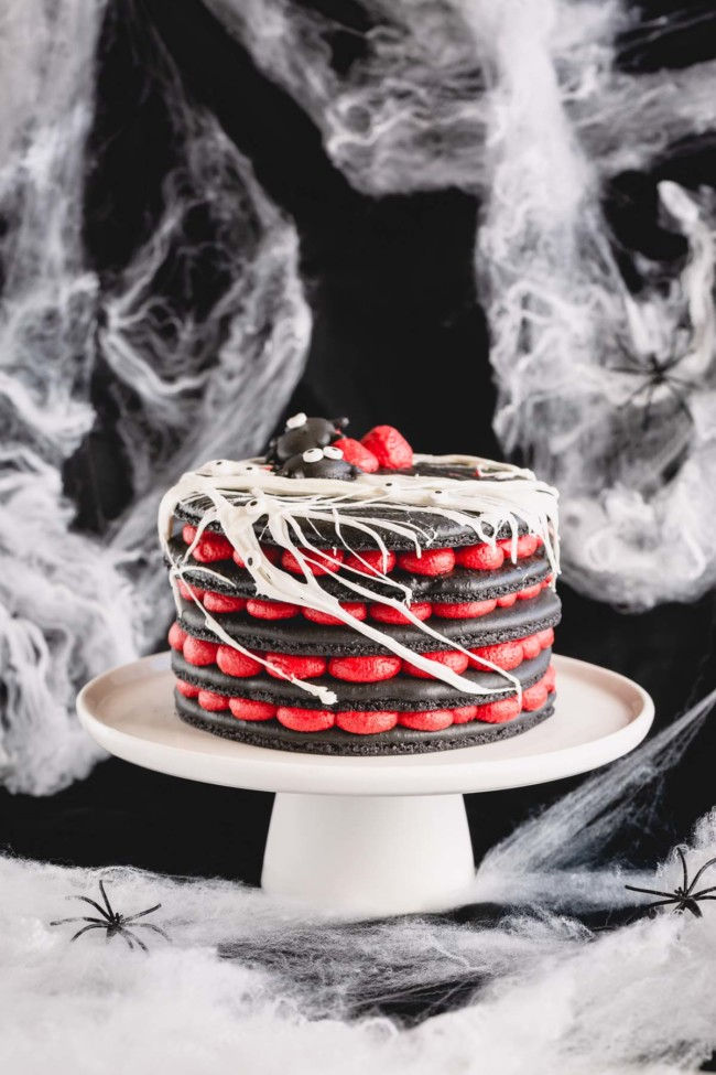 A 5-layer black macaron cake filled with red cream cheese filling on a white cake stand.
