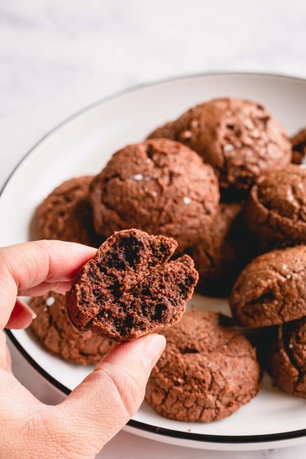 A plate of brownie cookies with one cookie broken in half.