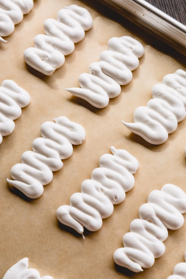 White meringue piped into zigzag pattern to create mummy.