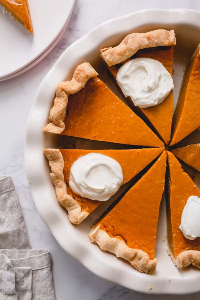 Overhead shot of sliced pumpkin pie in a pie dish.