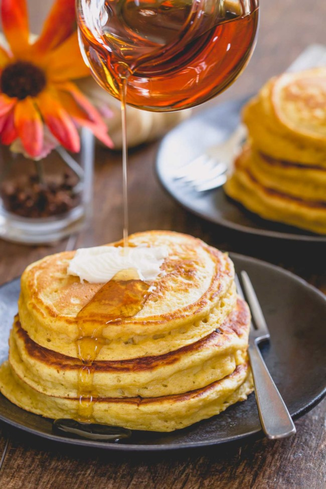 3 pumpkin pancakes stacked on a plate with a slice of butter and maple syrup being poured on top.